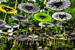 Bunter Regenschirm des Grün- und Weißbuches, der im Himmel hängt stockfotos