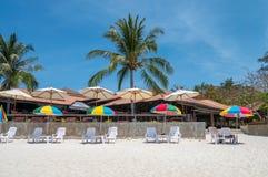 Bunter Regenschirm mit sunbed auf weißem Strand lizenzfreies stockbild