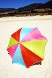 Bunter runder Regenschirm auf weißem sandigem Strand mit sonnigem blauem Himmel. Lizenzfreie Stockbilder