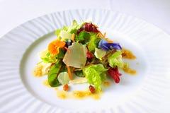 Bunter Salat mit Kopfsalat, Käse, Blumen und Rosinen Stockfotos