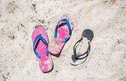 Bunter sandiger Flip Flops auf dem Strand an einem Sommertag stockfotografie