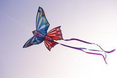 Bunter Schmetterlingsdrachen mit hellen Bändern fliegt in den Himmel stockbild