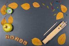 Bunter Schulehintergrund Schreibtischoberfläche mit Uhr, Apfel, Koch Stockfotos