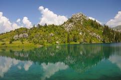 Bunter See mit Bergen, Himmel und Wolken Stockfotografie