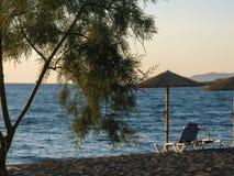 Bunter Sonnenuntergang über leeren Sandy Beach Unscharfe Postkarte des Baums, des Strand-Stuhls, des Straw Umbrellas und des blau lizenzfreies stockbild