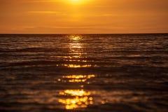 bunter Sonnenuntergang über Strand des ruhigen Sees mit dunkelblauem Wasser und drastischen contrasty Wolken lizenzfreie stockbilder