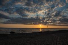 bunter Sonnenuntergang über Strand des ruhigen Sees mit dunkelblauem Wasser und drastischen contrasty Wolken stockbild