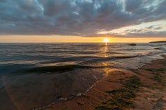 bunter Sonnenuntergang über Strand des ruhigen Sees mit dunkelblauem Wasser und drastischen contrasty Wolken stockfotografie