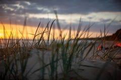 bunter Sonnenuntergang über Strand des ruhigen Sees mit dunkelblauem Wasser und drastischen contrasty Wolken stockfoto