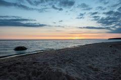 bunter Sonnenuntergang über Strand des ruhigen Sees mit dunkelblauem Wasser und drastischen contrasty Wolken lizenzfreies stockfoto