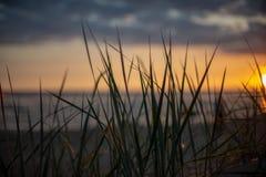 bunter Sonnenuntergang über Strand des ruhigen Sees mit dunkelblauem Wasser und drastischen contrasty Wolken lizenzfreie stockfotografie