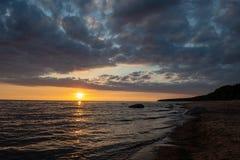 bunter Sonnenuntergang über Strand des ruhigen Sees mit dunkelblauem Wasser und drastischen contrasty Wolken lizenzfreies stockbild