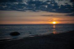 bunter Sonnenuntergang über Strand des ruhigen Sees mit dunkelblauem Wasser und drastischen contrasty Wolken stockbilder