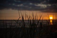 bunter Sonnenuntergang über Strand des ruhigen Sees mit dunkelblauem Wasser und drastischen contrasty Wolken lizenzfreie stockfotos