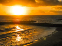 Bunter Sonnenuntergang durch den Ozean und den Strand Stockbilder