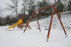 Bunter Spielplatz in einem Park während des Schneesturmes Stockbilder