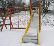 Bunter Spielplatz in einem Park während des Schneesturmes Stockfotografie