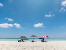Bunter Strandschirm, weißer Strand und blauer Himmel Lizenzfreies Stockfoto