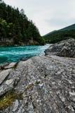 Bunter Türkisfluß und -ufer mit Felsen und Bäumen in Norwegen Stockfotografie