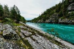 Bunter Türkisfluß und -ufer mit Felsen und Bäumen in Norwegen Lizenzfreies Stockfoto