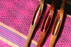 Bunter Thread in der Holzspule auf Seidengewebe Stockfotos