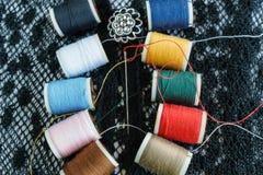 Bunter Thread und Nadel auf schwarzem Gewebe Stockfotos