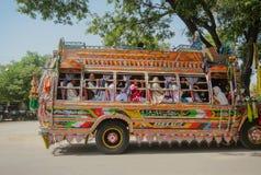 Bunter verzierter Bus mit pakistanischen Männern und Frauenpassagieren stockfotos