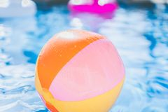Bunter Wasserball, der in Swimmingpool schwimmt Abstrakter Begriff von Sommerferien, Entspannung und haben Spaß in Stockfoto