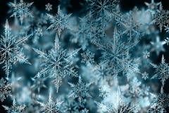Bunter Weihnachtshintergrund mit Schneeflocken und Sternen auf einem Blauen Stockfotos