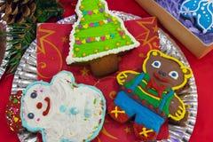 Bunter Weihnachtslebkuchen auf einem roten Hintergrund stockbilder