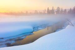 Bunter Wintersonnenuntergang im Wald und im Fluss mit schönem nebelhaftem Lizenzfreie Stockfotos