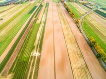 Buntes Ackerland gesehen von der Vogel ` s Augenansicht Ländliche Landschaft mit einer Straße von der Luft Lizenzfreies Stockfoto