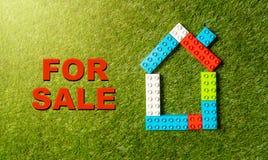Buntes Bauklotzhaus und für den Verkaufstext geschrieben auf grünes Gras in Investitions-Immobiliensektor lizenzfreie stockbilder