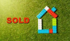 Buntes Bauklotzhauswort Sold geschrieben auf Gras Konzept in des wirklichen Zustandes und Immobiliensektor lizenzfreie stockfotografie