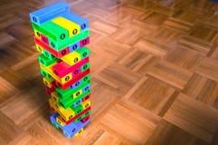 Buntes Blockspiel jenga auf hölzernem Hintergrund Stockbilder