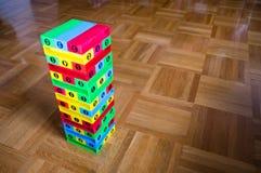 Buntes Blockspiel jenga auf hölzernem Hintergrund Lizenzfreies Stockfoto