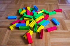 Buntes Blockspiel zerstreut auf hölzernen Hintergrund Lizenzfreies Stockfoto
