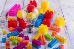 Buntes Blockspielzeug und Glühlampe auf weißem Boden Lizenzfreies Stockfoto