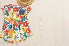 Buntes Blumenbabykleid und -strohhut auf einem hellgrauen hölzernen Hintergrund Babysommermode-accessoires Draufsicht, Kopienbade Lizenzfreies Stockfoto