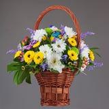 Buntes Blumenblumenstrauß-Anordnungsmittelstück im Weidenkorb stockfotografie
