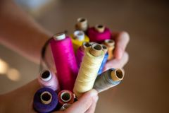 Buntes Bobins in den Mädchenhänden lizenzfreies stockfoto