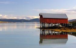 Buntes Bootshaus reflektierte sich im Fjordwasser Lizenzfreie Stockfotos