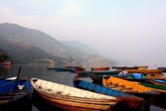 Buntes Bootssymbol des Phewa Seeufers mit Nebel morgens in Nepal lizenzfreie stockfotografie