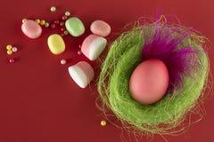Buntes Ei Ostern mit einer schönen rosa Feder in einem Nest stockfoto
