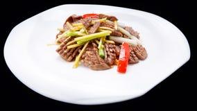 Buntes Fleisch und Gemüse brät gekocht werden lokalisiert auf schwarzem Hintergrund, chinesische Küche an Stockbilder