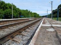 Buntes Foto der Eisenbahn unter dem Waldgürtel an einem klaren sonnigen Tag Stockfotografie