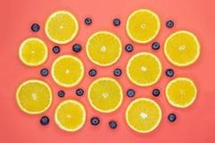 Buntes Fruchtmuster von frischen orange Scheiben und von Blaubeeren auf korallenrotem Hintergrund stockbilder