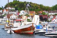 Buntes hölzernes Boot auf dem Wasser mit einer Piratenflagge Lizenzfreies Stockbild