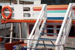 Buntes hölzernes Bootsdeck mit Lebenboje Glücklicher Schiffskreuzfahrthintergrund Stockfotos