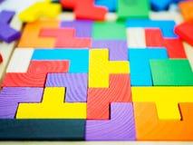 Buntes hölzernes Puzzlespiel auf weißem Hintergrund Stockbilder